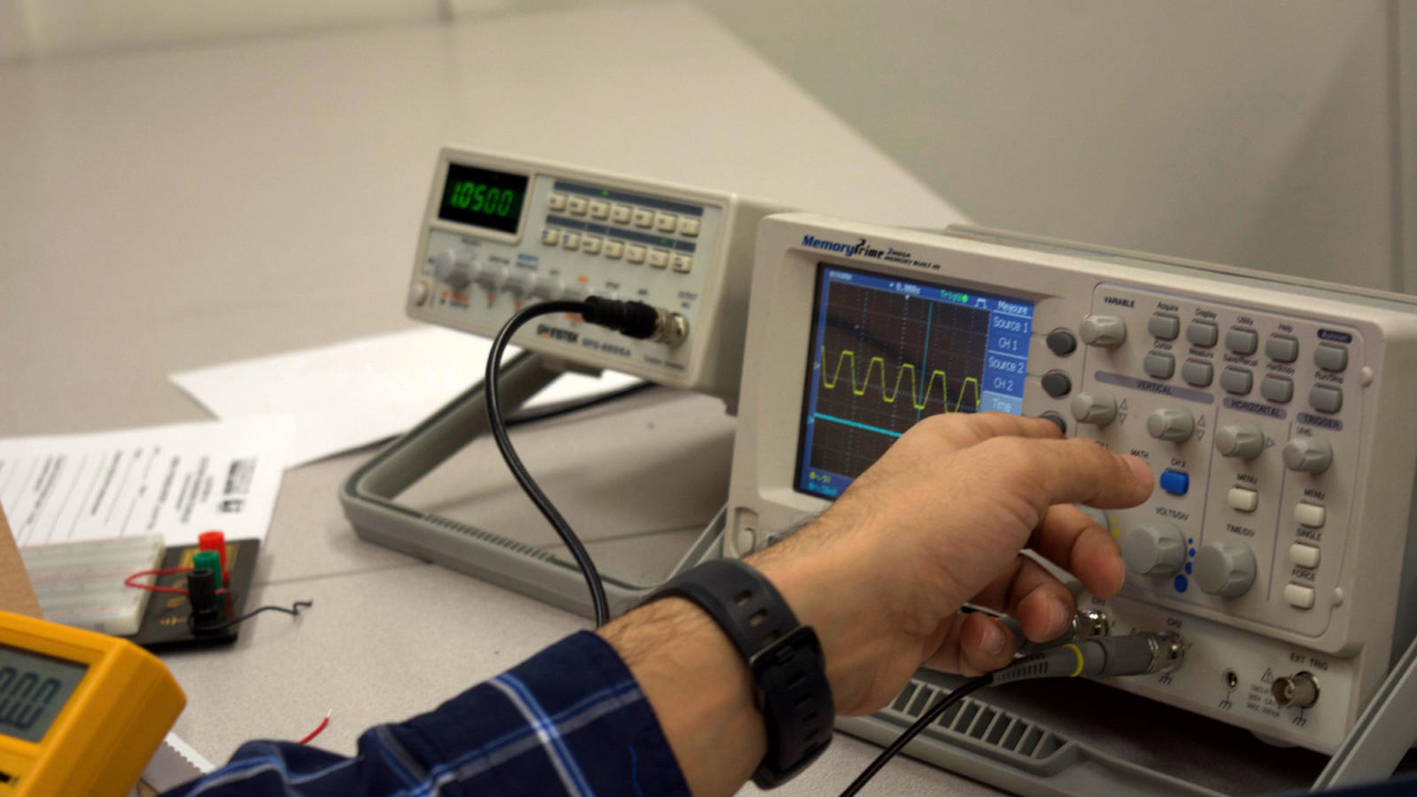 An electronics student adjusts an oscilloscope to measure voltage change in a circuit.