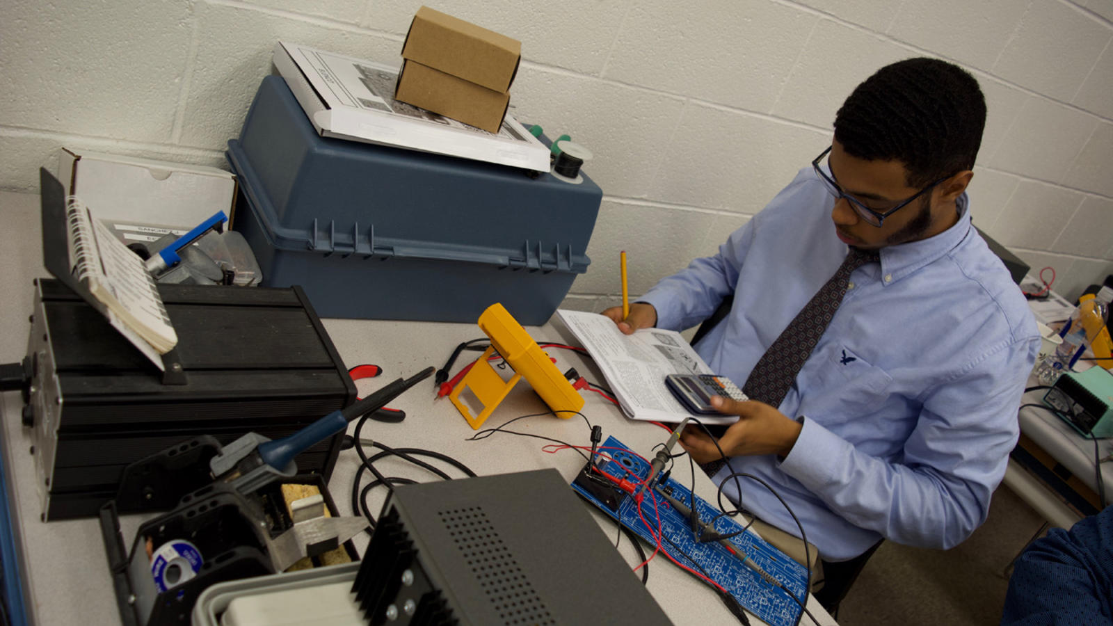 An electronics tech performs calculations using a calculator and readings from a multi-tester.