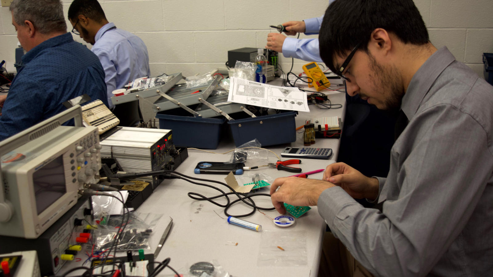 An Allentown electronics tech student prepares a circuit board for soldering.