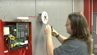 An Electrical student learns how to wire an alarm system.