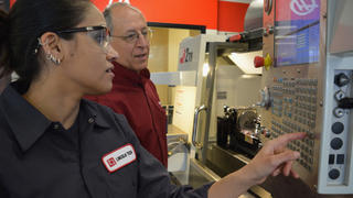 A Female CNC Student learns how to operate a Haas CNC Machine