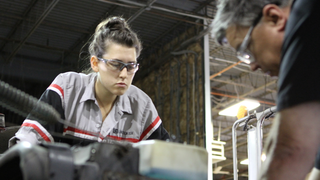A Lincoln Tech Student works with her instructor on a diesel truck engine.