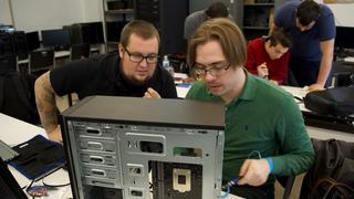 Two Allentown students discuss construction of a desktop computer tower.