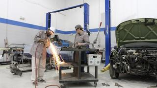 An auto body student works with a pneumatic cutter on a small steel structural piece - wide angle