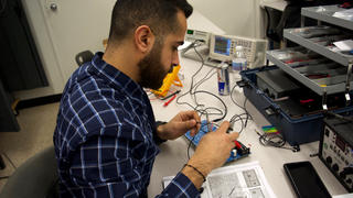 An electronics tech trainee at the Allentown campus tests a circuit board.