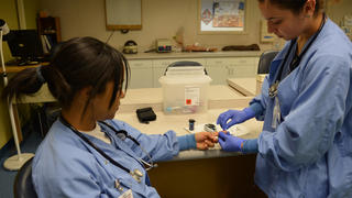 Two medical assistant students practice fingertip blood glucose serum testing.